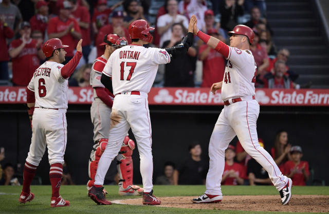 Los Angeles Angels' Justin Bour, right, is congratulated by Shohei Ohtani (17) and David Fletcher, left, as Cincinnati Reds catcher Curt Casali stands at the plate during the eighth inning of a baseball game Wednesday, June 26, 2019, in Anaheim, Calif. (AP Photo/Mark J. Terrill)