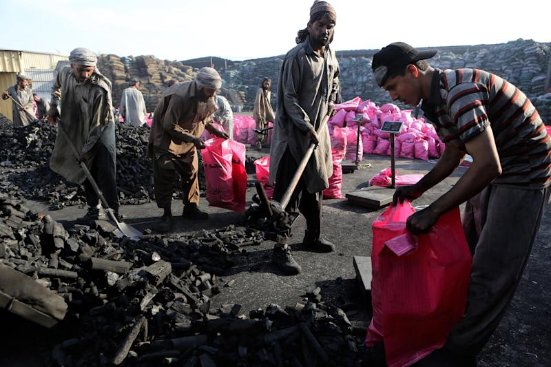 In this Thursday Dec. 5, 2013 photo, workers fill plastic bags with charcoal believed to be from Somalia at a charcoal trading facility in Sharjah, United Arab Emirates. Charcoal from Somalia is prized in Gulf nations: Made from acacia trees, it's slow burning and gives a sweet aroma to the region's beloved grilled meats and waterpipes. It is also banned by the United Nations, because its shipments rake in millions of dollars a year for al-Qaida-linked militants. (AP Photo/Kamran Jebreili)