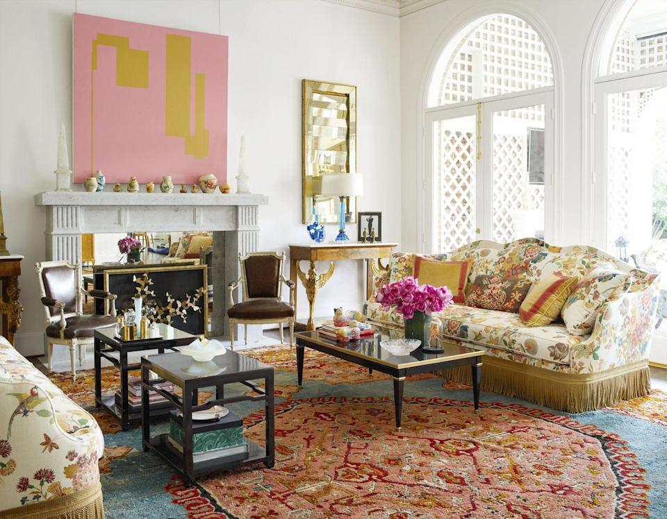 """<p>Warm, silky white walls create an airy canvas for a vibrant painting by Pete Jordan and a decorative Oushak rug in this <a href=""""https://www.veranda.com/home-decorators/a29416531/kimberly-schlegel-whitman-dallas-home-tour/"""" rel=""""nofollow noopener"""" target=""""_blank"""" data-ylk=""""slk:Dallas family room"""" class=""""link rapid-noclick-resp"""">Dallas family room</a> designed by <a href=""""https://www.janshowers.com/"""" rel=""""nofollow noopener"""" target=""""_blank"""" data-ylk=""""slk:Jan Showers"""" class=""""link rapid-noclick-resp"""">Jan Showers</a>. To make the expansive room feel less daunting, architect <a href=""""https://www.wilsonfuqua.com/"""" rel=""""nofollow noopener"""" target=""""_blank"""" data-ylk=""""slk:J. Wilson Fuqua"""" class=""""link rapid-noclick-resp"""">J. Wilson Fuqua</a> added custom crown moldings—depicting tassels and latticework—to bring a playful element to the space. The sofa is upholstered in a flamboyant <a href=""""https://www.fschumacher.com/"""" rel=""""nofollow noopener"""" target=""""_blank"""" data-ylk=""""slk:Schumacher"""" class=""""link rapid-noclick-resp"""">Schumacher</a> floral linen with <a href=""""https://samuelandsons.com/"""" rel=""""nofollow noopener"""" target=""""_blank"""" data-ylk=""""slk:Samuel & Sons"""" class=""""link rapid-noclick-resp"""">Samuel & Sons</a> fringe.</p>"""