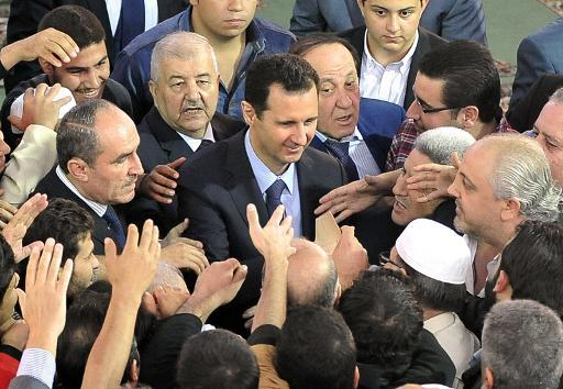 A picture released by the official Syrian Arab News Agency (SANA) on October 15, 2013 shows President Bashar al-Assad being greeted by supporters following Eid al-Adha prayers in Damascus