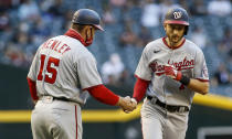 Washington Nationals' Trea Turner, right, is congratulated by third base coach Bob Henley after hitting a home run against the Arizona Diamondbacks during the first inning of a baseball game Friday, May 14, 2021, in Phoenix. (AP Photo/Darryl Webb)