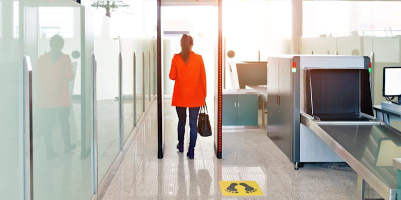 Female passenger walking through the airport security checkpoint.