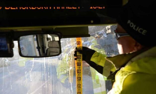 An Ottawa police officer measures the position of a sunshade on a double-decker bus used to simulate and record conditions of the Westboro bus crash on the day after the crash on Jan. 12, 2019. (Trial Exhibit/Ontario Court of Justice - image credit)