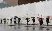 People under umbrellas practice social distancing as they line up for early voting, Friday, Oct. 30, 2020, in the Brooklyn borough of New York. The national election is Nov. 3. (AP Photo/Mark Lennihan)