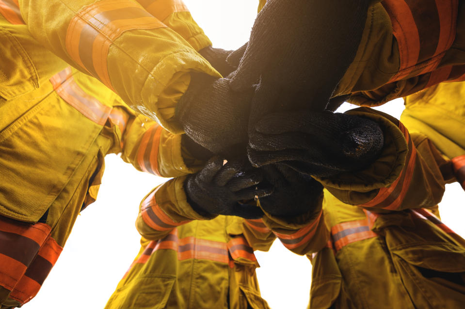 Firefighter putting hands up for fire fighting.