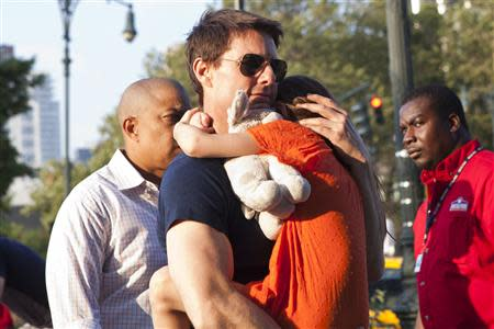 Actor Tom Cruise carries his daughter Suri into the Chelsea Piers sports facility in New York