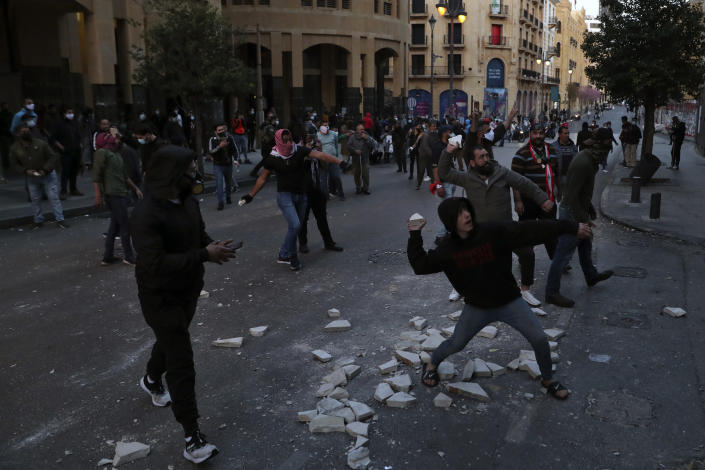 Anti-government protesters throw stones towards police near Parliament Square, In Beirut, Lebanon, Saturday, March. 13, 2021. Riot police fired tear gas to disperse scores of people who protested near parliament building in central Beirut Saturday amid deteriorating economic and financial conditions and as the local currency hit new low levels. (AP Photo/Bilal Hussein)