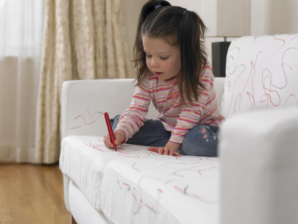 Young girl drawing on a white sofa with a red pen