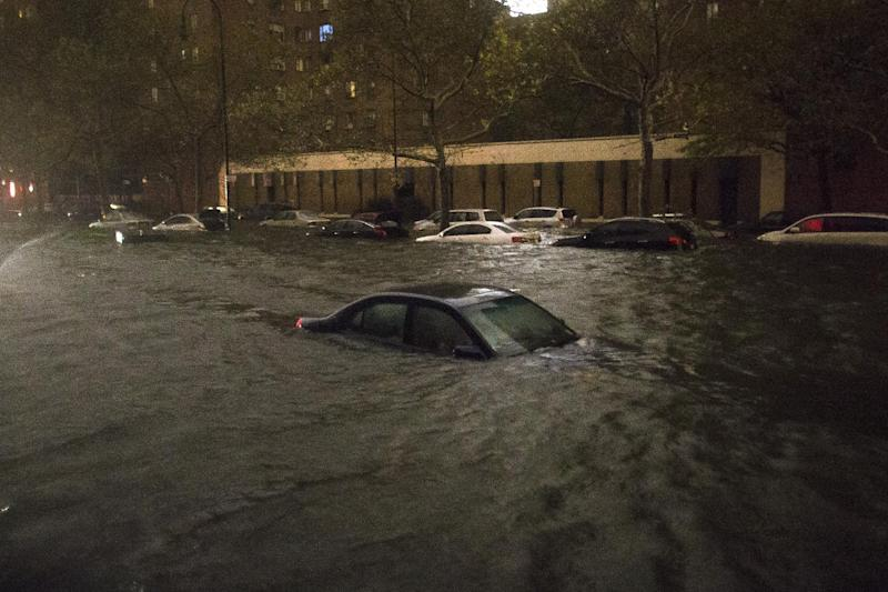 FILE-In this Monday, Oct. 29, 2012, file photo, a vehicle is submerged on 14th Street near the Consolidated Edison power plant, in New York. Alarming claims that hundreds of thousands of flood-damaged cars from Superstorm Sandy will inundate the used car market aren't backed up by insurance company claim data, The Associated Press has found. The dire predictions come mostly from companies that track vehicle title and repair histories and sell those reports. (AP Photo/ John Minchillo, File)