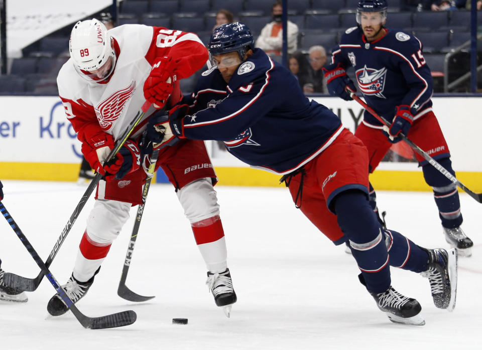 Columbus Blue Jackets defenseman Seth Jones, front right, checks Detroit Red Wings forward Sam Gagner during the first period of an NHL hockey game in Columbus, Ohio, Saturday, May 8, 2021. (AP Photo/Paul Vernon)