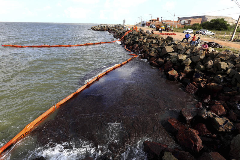 This Oct. 4, 2019 handout photo released by the Aracaju Municipal Press Office, shows rocks stained by an oil spill, on Artistas Beach, in Aracaju, Brazil. The oil that has been polluting Brazil's northeastern beaches since early September is likely coming from Venezuela, according to a report by Brazil's state oil company cited by the country's environment minister. (Andre Moreira/Aracaju Municipal Press Office via AP)