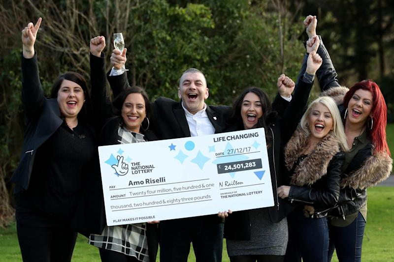 Taxi driver Amo Riselli, 50, with his daughters celebrating the win at a National Lottery photo call: PA