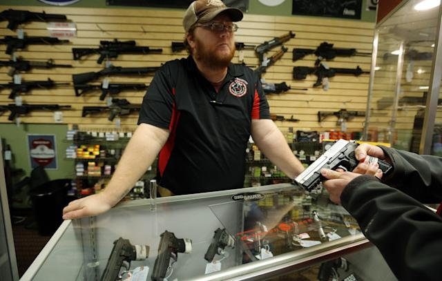 Metro Shooting Supplies' employee Chris Cox speaks to a customer about the purchase of a 9mm handgun in Bridgeton, Missouri
