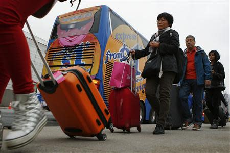 Passengers line up to board a Megabus bus in New York City