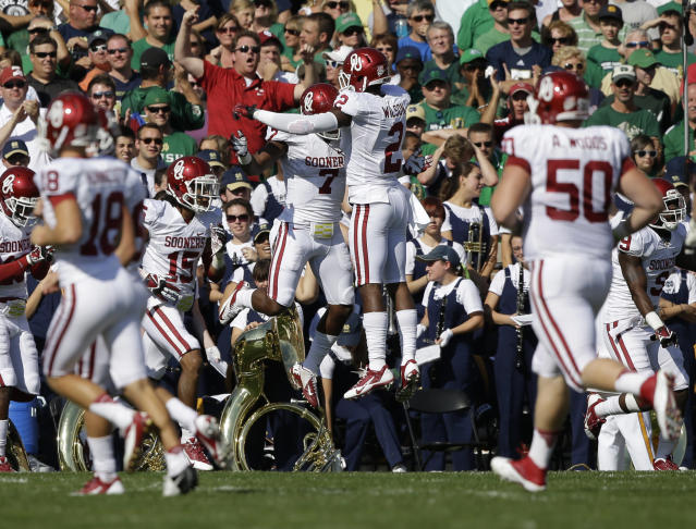 Oklahoma's Corey Nelson (7) celebrates with Julian Wilson (2) after intercepting a pass by Notre Dame 's Tommy Rees pass and ran it in 24-yards for a touchdown during the first half of an NCAA college football game on Saturday, Sept. 28, 2013, in South Bend, Ind. (AP Photo/Darron Cummings)