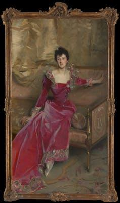19th-century portrait of woman in a red dress sitting on a chaise Longue.