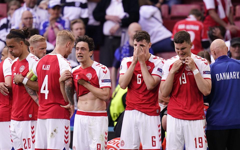 Players of Denmark react while their teammate Christian Eriksen receives medical treatment