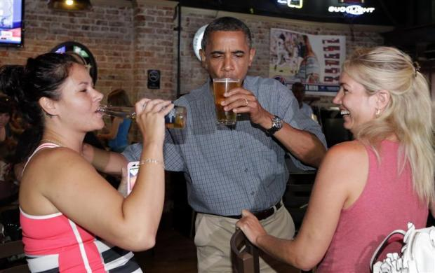 President Barack Obama enjoys a beer with Jennifer Klanac (L) and Suzanne Woods (R) at Ziggy's Pub in Amherst, Ohio July 5, 2012.