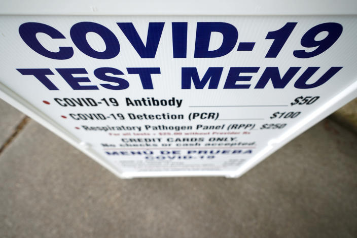 A sign outside Principle Health Systems and SynerGene Laboratory lists COVID-19 tests available Tuesday, April 28, 2020, in Houston. The company, which opened two new testing sites Tuesday, is now offering a new COVID-19 antibody test developed by Abbott Laboratories. (AP Photo/David J. Phillip)