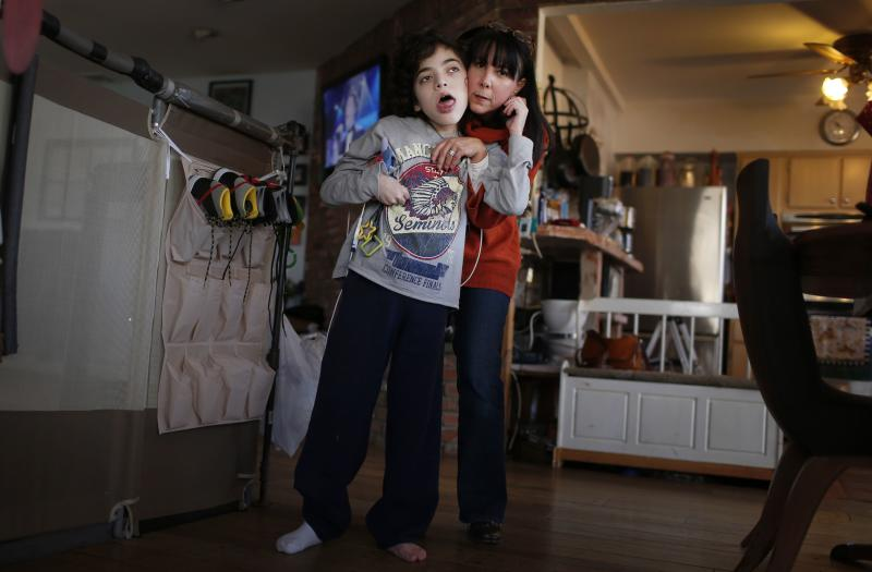 Missy Miller (R) poses with her epileptic son Oliver in their home at Atlantic Beach, New York January 7, 2014. Oliver suffered a brain stem injury in utero and now, at 14, has hundreds of seizures a day. For months, his family has pinned their hopes on a strain of marijuana developed in Colorado that has helped children with similar conditions. But under an executive order by Governor Andrew Cuomo on Wednesday making New York the 21st state to allow medical marijuana, it will remain illegal to grow marijuana or to import specialized plants from other states. Patients will have little say in the marijuana they are prescribed and people like Oliver - who could benefit from a specialized strain known as Charlotte's Web that is high in the compound cannabidiol, or CBD, - would be cut out entirely. Picture taken January 7, 2014. REUTERS/Mike Segar (UNITED STATES - Tags: HEALTH POLITICS)