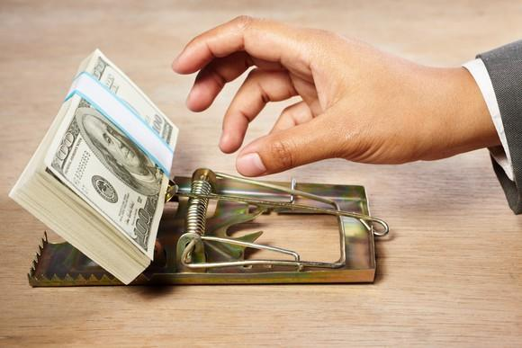 A person reaching for a stack of hundred dollar bills laid in a mouse trap.
