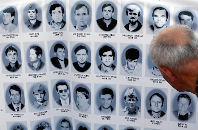 <p>A man looks at a banner with pictures of Serbs killed by Bosnian forces during the 1992-95 Bosnian war in the Srebrenica area, in downtown Belgrade, Serbia, Monday, July 10, 2017. (Photo: Amel Emric/AP) </p>