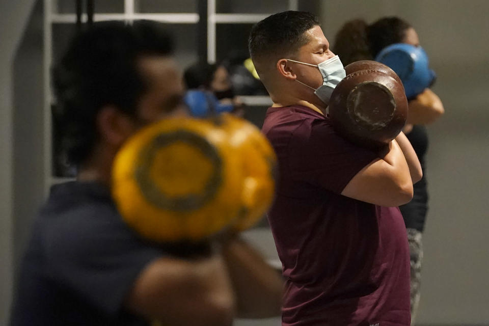 Juan Avellan, center, and others wear masks while working out in an indoor class at a Hit Fit SF gym amid the coronavirus outbreak in San Francisco, Tuesday, Nov. 24, 2020. (AP Photo/Jeff Chiu)
