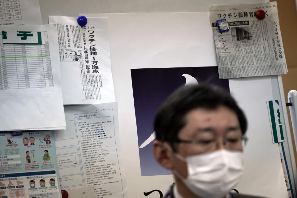 Newspapers' clips on COVID-19 vaccination are posted on a board as Hitoshi Iwase, head of the local office for COVID-19 vaccination preparation at Tokyo's Sumida ward office works Friday, Jan. 22, 2021. Japan is accelerating preparations for COVID-19 vaccinations in hopes of starting them in late February, but uncertainty is growing as the country faces vaccine-shy public, slow approval process and bureaucratic roadblocks, casting a doubt if Tokyo Olympic this summer is possible. (AP Photo/Eugene Hoshiko)