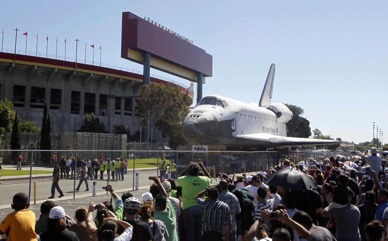 The space shuttle Endeavour moves north on Bill Robertson Lane in front of the Coliseum in Los Angeles Sunday, Oct. 14, 2012. In thousands of Earth orbits, the space shuttle Endeavour traveled 123 million miles. But the last few miles of its final journey are proving hard to get through. Endeavour's 12-mile crawl across Los Angeles to the California Science Museum hit repeated delays Saturday, leaving expectant crowds along city streets and at the destination slowly dwindling. Officials estimated the shuttle, originally expected to finish the trip early Saturday evening, would not arrive until later Sunday. (AP Photo/Alex Gallardo)