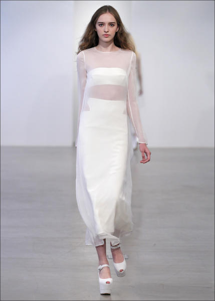 In this undated image released by Calvin Klein, a model wears a sheer ivory T-shirt over an ivory silk skirt and bandeau by Calvin Klein. True to form, the Calvin Klein resort collection is built on clean, architectural lines, but creative director Francisco Costa strategically inserts softer shapes _ and the occasional sexy cutout.(AP Photo/Calvin Klein)