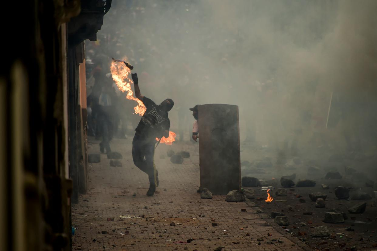 A demonstrator throws a Molotov cocktail at riot police during clashes in Quito, as thousands march against Ecuadorean President Lenin Moreno's decision to slash fuel subsidies, on Oct. 9, 2019. (Photo: Rodrigo Buendia/AFP via Getty Images)