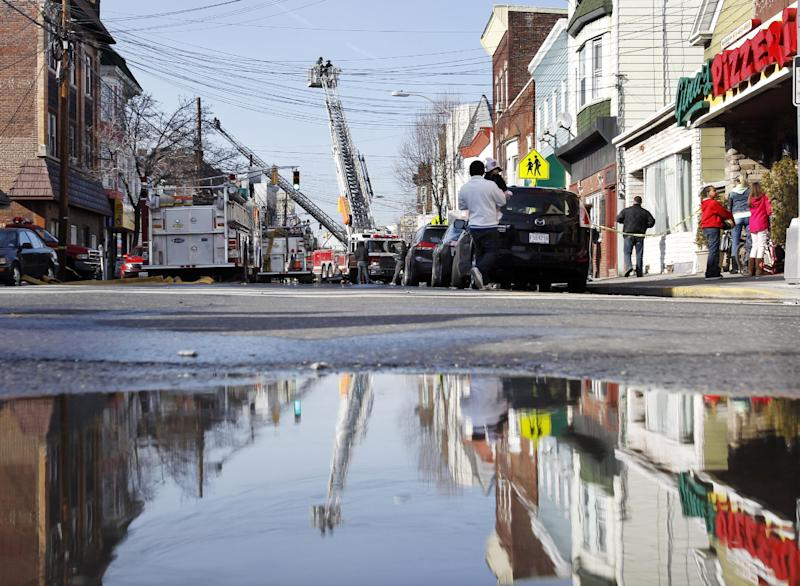 Firefighters battle a five-alarm fire at a building in Harrison, N.J., Sunday, March 10, 2013. The blaze gutted a two-story building with a restaurant on the ground floor and then spread to a two-story residential building. There are reports of at least four firefighters sustaining minor injuries. (AP Photo/Mel Evans)