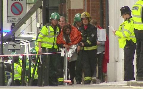 <span>A woman with blankets wrapped around her is escorted by emergency services</span> <span>Credit: Sky/AP </span>