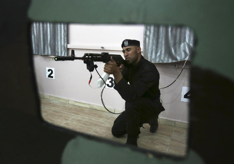 """Palestinian security officer Ahed Abu Shabban, 23, aims an electronically-modified AK-47 rifle at the headquarters of the security training department of the Hamas interior ministry in Gaza City, in the northern Gaza Strip on Thursday, April 10, 2014. Adnan Abu Amer, an expert on Palestinian militant groups at Gaza's Al Ummah University, says the prices of some weapons have nearly doubled in recent months, and the price of ammunition has tripled. """"The most significant result of the tunnel demolitions has been the scarcity of weapons, ammunition and explosives,"""" he says. (AP Photo/Adel Hana)"""