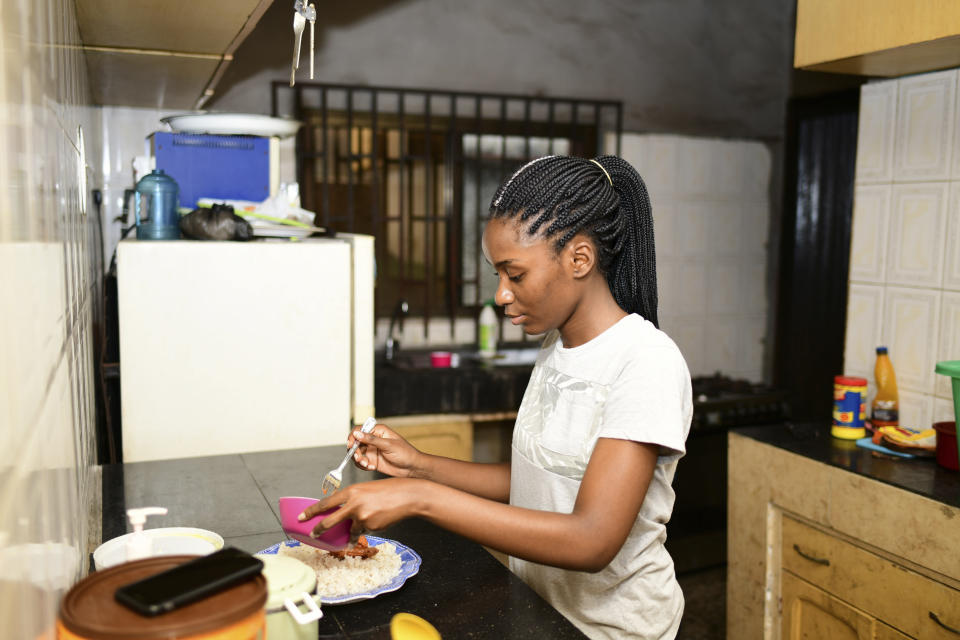 In this photo taken on Wednesday, Oct. 14, 2020, Dodeye Ewa, 16 year old serve breakfast at inside the kitchen in Calabar, Nigeria. The third child is bothered by President Donald Trump's rhetoric and his policies toward international students, most recently one announced Friday that limits their stays in the U.S. to two or four years with uncertainty about whether their visas will be extended. (AP Photo/Daniel H Williams )