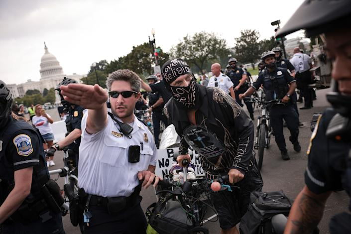 A counter-protestor is escorted out of the rally site by police officers as supporters of those charged in the January 6 attack on the U.S. Capitol attend the 'Justice for J6' rally near the U.S. Capitol September 18, 2021 in Washington, DC.