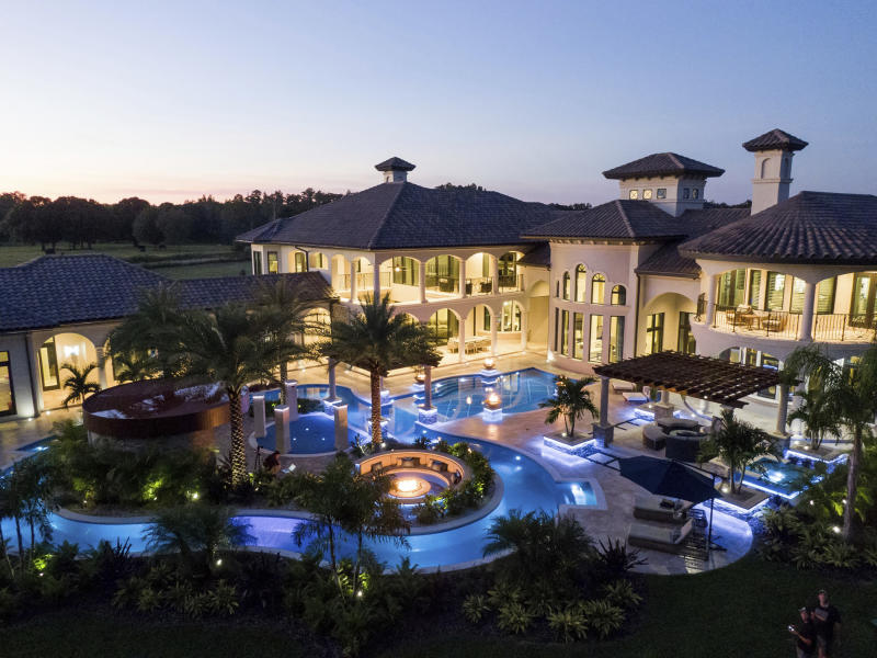 This 2018 photo provided by Ryan Hughes of Ryan Hughes Design Build shows an outdoor space at a home in Florida. Tampa-based designer Hughes created a lazy river, with water curtains and places to lounge around a firepit. (Joe Traina/Ryan Hughes via AP)