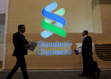 People pass by the logo of Standard Chartered plc at the SIBOS banking and financial conference in Toronto, Ontario, Canada October 19, 2017. REUTERS/Chris Helgren/Files
