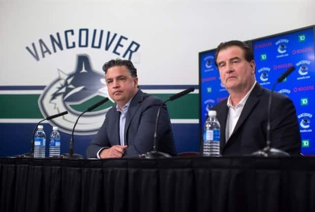 Vancouver Canucks head coach Travis Green, left, and general manager Jim Benning are pictured speaking to reporters on Friday.  (Darryl Dyck/The Canadian Press - image credit)