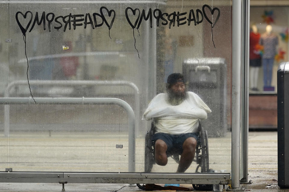 A man takes cover in a bus stop shelter as Hurricane Ida begins to make landfall, Sunday, Aug. 29, 2021, in New Orleans, La. (AP Photo/Eric Gay)