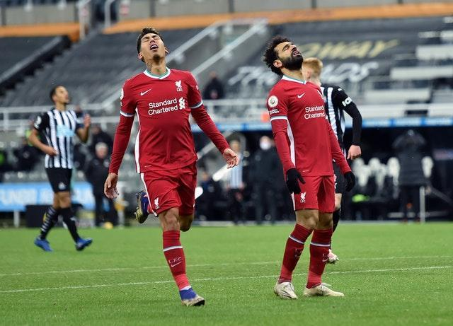 Roberto Firmino and Mohamed Salah react to a missed chance