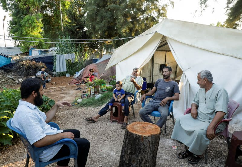 Hossam Kaheil sits with his neighbors at a camp for internally displaced people in Idlib