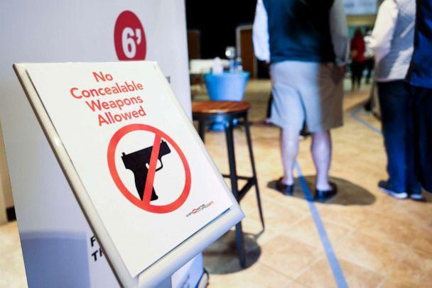 PHOTO: A sign prohibits concealed weapons as people wait to cast their in-person absentee ballots at Seacoast Church West Ashley, Oct. 30, 2020 in Charleston, S.C.  (Michael Ciaglo/Getty Images)