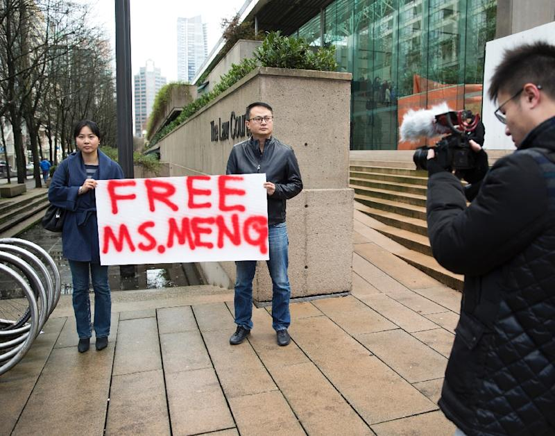 Two demonstrators outside a courthouse in Vancouver on December 10, 2018 call for the release of Huawei executive Meng Wanzhou after she was detained for possible extradition to the US for alleged sanctions busting