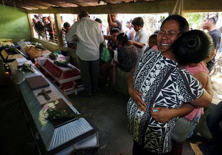 A relative cries near coffins with the bodies of the victims after a military helicopter crashed on top of two vans in an open field while trying to land, in Santiago Jamiltepec