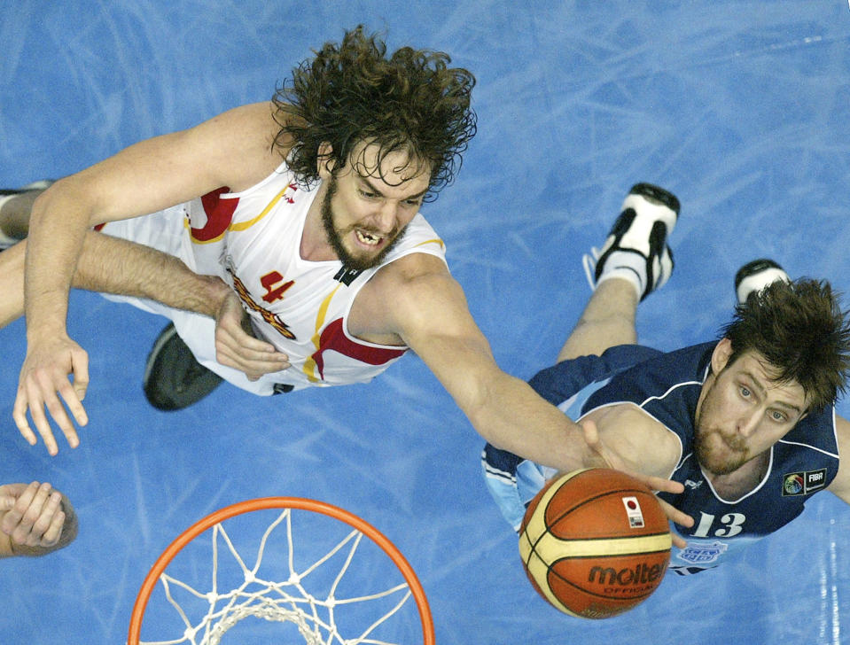 FILE - In this Sept. 1, 2006, file photo, Spain's Pau Gasol, left, goes after a rebound along with Argentina's Andres Nocioni during the semifinals of the World Basketball Championships in Saitama, Japan. The 2006 world championship was perhaps the last truly wide-open international basketball event. Argentina arrived as the Olympic champion and Spain left as the world champion, the last time for a long while anyone other than the U.S. would hold either title. (AP Photo/Mark J. Terrill, File)