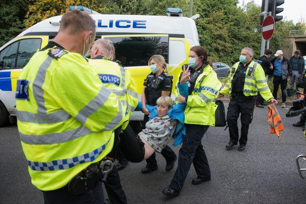 Police officers arrest an Insulate Britain climate activist who had been blocking a slip road from the M25 on Monday (Photo: Mark Kerrison via Getty Images)