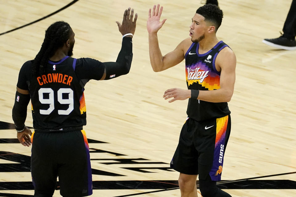 Phoenix Suns guard Devin Booker high fives teammate Jae Crowder (99) during the first half of an NBA basketball game against the Utah Jazz, Wednesday, April 7, 2021, in Phoenix. (AP Photo/Matt York)