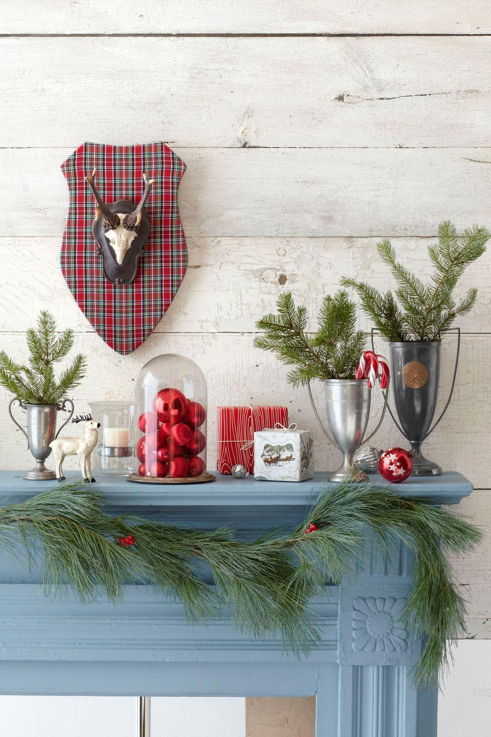 """<p>Give your mantel a rustic-preppy look with a <span class=""""redactor-unlink"""">resin reindeer ornament</span> and plaid plaque. Antique trophies make cute vases for pine tree boughs.</p><p><a class=""""link rapid-noclick-resp"""" href=""""https://go.redirectingat.com?id=74968X1596630&url=https%3A%2F%2Fwww.etsy.com%2Fmarket%2Fdeer_ornament&sref=https%3A%2F%2Fwww.countryliving.com%2Fhome-design%2Fdecorating-ideas%2Fadvice%2Fg1247%2Fholiday-decorating-1208%2F"""" rel=""""nofollow noopener"""" target=""""_blank"""" data-ylk=""""slk:SHOP DEER ORNAMENTS"""">SHOP DEER ORNAMENTS</a> </p>"""