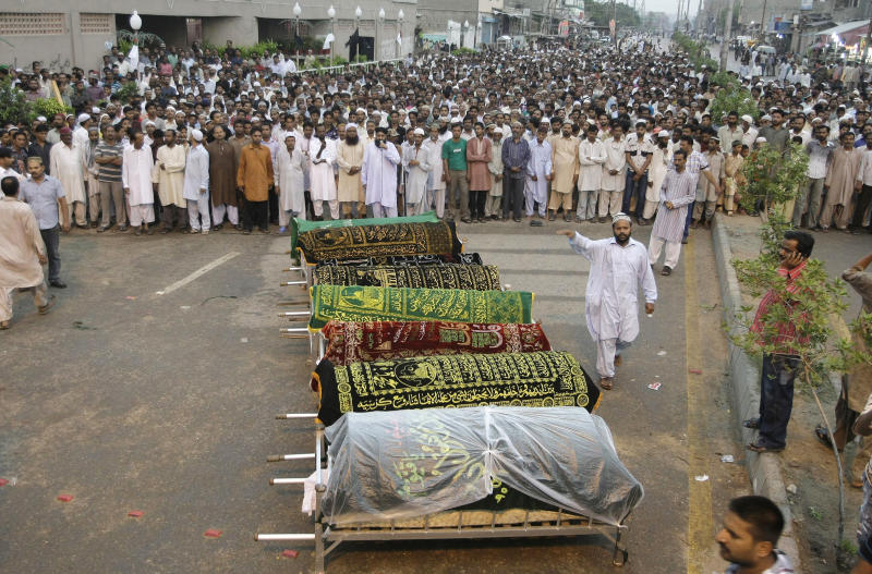 People get ready to offer funeral prayers of workers who lost their lives in a factory fire, Wednesday, Sept. 12, 2012 in Karachi, Pakistan. Pakistani officials say the death toll from devastating factory fires that broke out in two major cities has killed hundreds. (AP Photo/Fareed Khan)